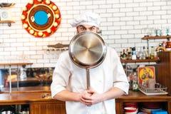 滑稽的年轻厨师厨师用煎锅盖了他的面孔 图库摄影