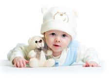 滑稽的婴孩有长毛绒玩具的weared帽子 免版税图库摄影