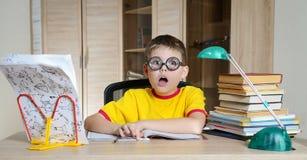 滑稽的玻璃的迷茫的男小学生尖叫在巨大的堆书附近 教育 有的男孩他的家庭作业的问题 免版税库存图片