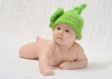 滑稽的绿色帽子的逗人喜爱的婴孩 免版税库存照片