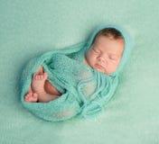 滑稽睡觉新出生在蓝色毯子和在尿布 免版税库存照片