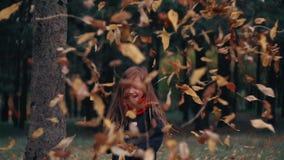 滑稽,快乐的逗人喜爱的小女孩跳投掷一个黄色秋天下落的叶子慢动作 股票录像