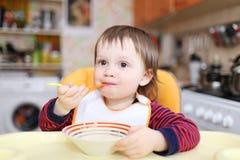 滑稽婴孩吃 免版税库存照片