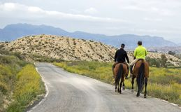 穆尔西亚,西班牙,2019年4月18日:两匹人骑乘马背面图沿路的 库存照片