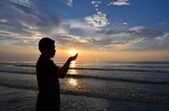 穆斯林剪影在海滩附近祈祷 库存照片