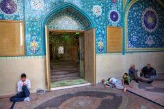 穆斯林在清真寺附近墙壁坐,在入口旁边 免版税库存照片