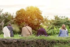 穆斯林在草坪中间坐早晨 库存照片