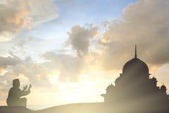 穆斯林年轻人为上帝读书在中间Ea的koran和平祈祷 库存照片