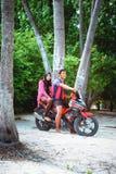 穆斯林年轻夫妇坐在海岛小村庄海滩的morcicle  库存照片