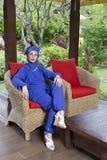 穆斯林的可爱的妇女在一把藤椅穿衣在庭院里 库存图片