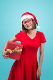穆巴拉克 圣诞老人 圣诞老人举行a的` s帽子的美丽的年轻亚裔妇女 图库摄影