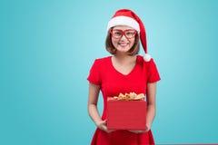 穆巴拉克 圣诞老人 圣诞老人举行a的` s帽子的美丽的年轻亚裔妇女 免版税库存图片