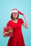 穆巴拉克 圣诞老人 圣诞老人举行a的` s帽子的美丽的年轻亚裔妇女 免版税库存照片