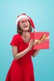 穆巴拉克 圣诞老人 圣诞老人举行a的` s帽子的美丽的年轻亚裔妇女 库存照片