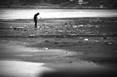 贫穷的人走在被污染的海滩的 库存图片