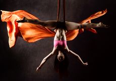 空中丝绸的,优美的曲解,杂技演员美丽的性感的舞蹈家执行在的一个把戏丝带 免版税库存照片