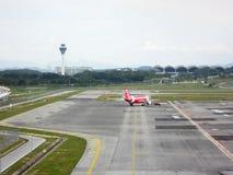 空中客车飞机由亚洲航空拥有拖曳并且准备离开 免版税库存图片