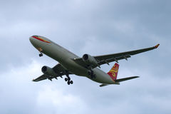 空中客车A330-343 (B-6527) -海南航空在多云天空飞行 免版税库存图片
