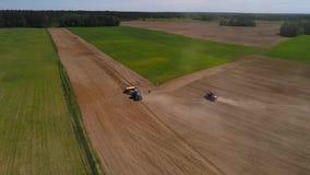 空中寄生虫射击了播种领域的两台拖拉机 在别的旁边的一台拖拉机中止 股票视频