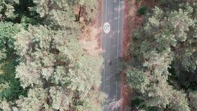 空中寄生虫观点的在公园骑自行车的桃红色球衣的年轻可爱的骑自行车者女孩 r 影视素材
