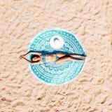 空中寄生虫观点的放松和晒日光浴在圆的绿松石海滩毛巾的泳装比基尼泳装的妇女在海洋附近 免版税库存图片