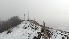 空中寄生虫:在山上面的妇女问候,冒险旅行癖概念、雪和云彩mistic冬天环境美化 影视素材