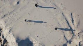 空中射击 三个人的顶视图在沙子互相进来 人的阴影 毒品交易 股票录像