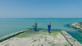 空中射击 唱歌在天蓝色的海岸、海滩或者码头的白肤金发的少妇与人音乐家键盘乐器演奏家性感的女孩舞蹈 股票视频