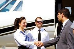 空中小姐和飞行员问候乘客 库存图片