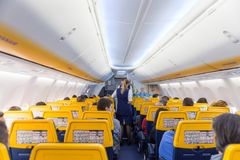 空中小姐在瑞安航空公司飞机飞行的服务passangers在2017年12月第14,在从的里雅斯特的一次飞行向巴伦西亚 免版税库存照片