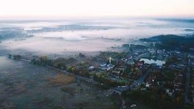 空中录影镜头 有雾的冷的早晨乡下 有薄雾的谷和领域包围的小富有的村庄 路 股票视频