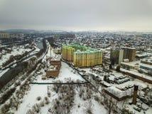 空中现代开发的城市郊区区域冬天顶视图与高楼、停放的汽车和建筑用起重机的 ?? 免版税库存照片