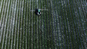 空中直升机射击了在种植园领域的拖拉机喷洒的水 影视素材