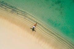 空中获得美丽的女孩寄生虫鸟瞰图在晴朗的热带海滩的乐趣 塞舌尔群岛 免版税库存图片