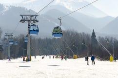 空中览绳推力在冬天多雪的山滑雪胜地的长平底船客舱 库存图片