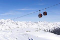 空中览绳推力缆车,在冬天多雪的山背景美好的风景的长平底船客舱 免版税库存照片