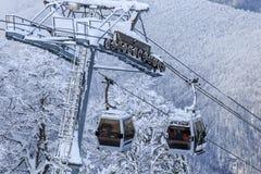 空中览绳在多雪的山背景美好的冬天风景的滑雪电缆车客舱 库存图片
