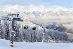 空中览绳在多雪的山背景美好的冬天风景的滑雪电缆车客舱 免版税库存图片