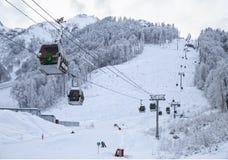 空中览绳在多雪的山背景美好的冬天风景的滑雪电缆车客舱 图库摄影