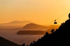 空中览绳或索道对山Srdj在杜布罗夫尼克,克罗地亚以日落为背景在海岛在海 库存照片