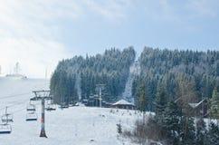 空中览绳推力在冬天多雪的山背景美好的风景的长平底船客舱 库存照片