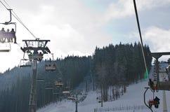 空中览绳推力在冬天多雪的山背景美好的风景的长平底船客舱 库存图片