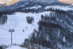 空中览绳滑雪电缆车在山坡背景的长平底船客舱在日落美好的冬天风景 库存图片