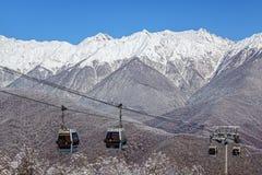 空中览绳滑雪电缆车在蓝天和多雪的山峰背景美好的冬天风景的长平底船客舱 库存图片