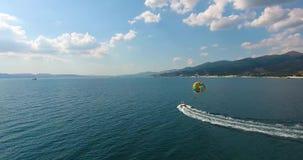 空中飞行快艇漂浮天蓝色的海表面上并且通过空气拉扯与游人的parasail 影视素材