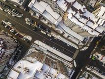 空中黑白现代城市冬天顶视图有高楼,停放的和移动的汽车的沿有路标的街道 库存图片