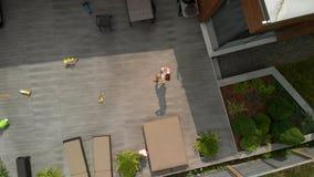 空中:有她的男婴儿子兄弟的年轻母亲在他们的在他们的庭院的时间-家庭价值观温暖的颜色 影视素材