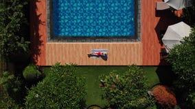 空中-上升在晒日光浴在毛巾的美丽的年轻女人上在红色比基尼泳装和草帽的游泳场附近在回归线 股票视频