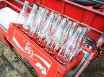 空回收瓶在红色塑料盒的可乐 免版税库存照片