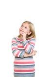 空想家一点 看快乐的小女孩握在下巴的手指和  免版税库存照片